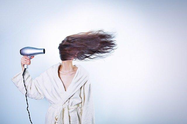 žena sušící si vlasy